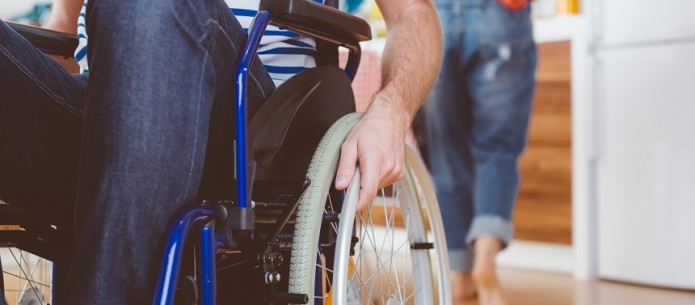 Disabled man sitting in a wheelchair in the domestic kitchen. Close up of leg and hand, unrecognizable person.